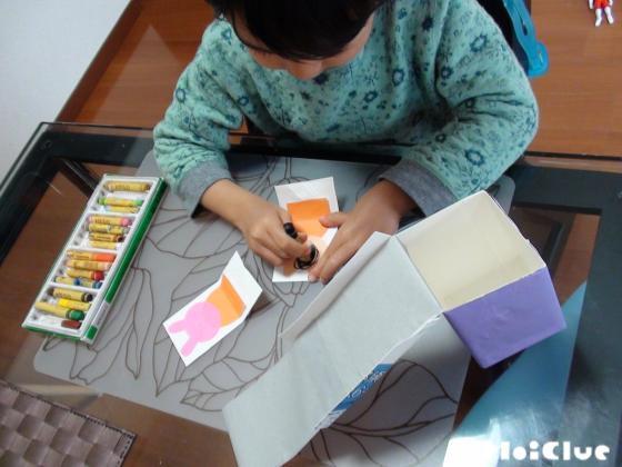 牛乳パックの台紙に折り紙の動物を貼り顔を描く子どもの様子