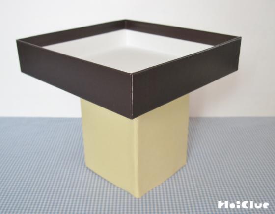 切った牛乳パックに空き箱の蓋をのせてさんぽうを作った写真