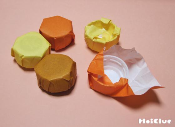 ペットボトルキャップを折り紙で包んでいる写真