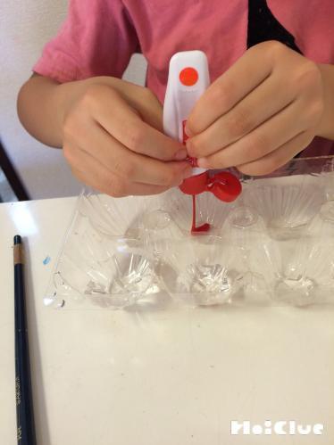 卵パックのくぼみに絵の具を垂らしている写真