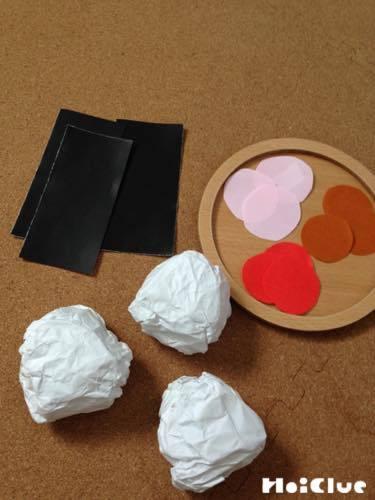 白い紙を丸めたものと黒い紙を細長く切ったものと赤い丸く切った画用紙などの写真