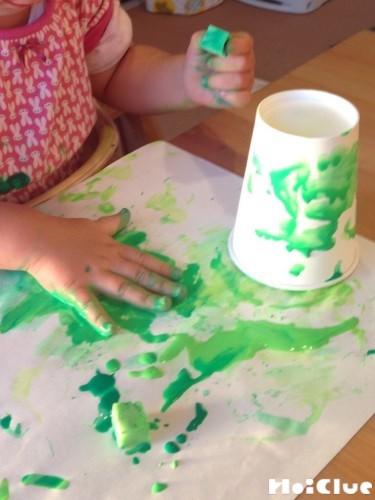 紙コップに絵の具を塗りつけている写真